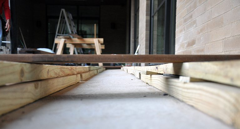 Shimming deck joists flush to the underside of the window